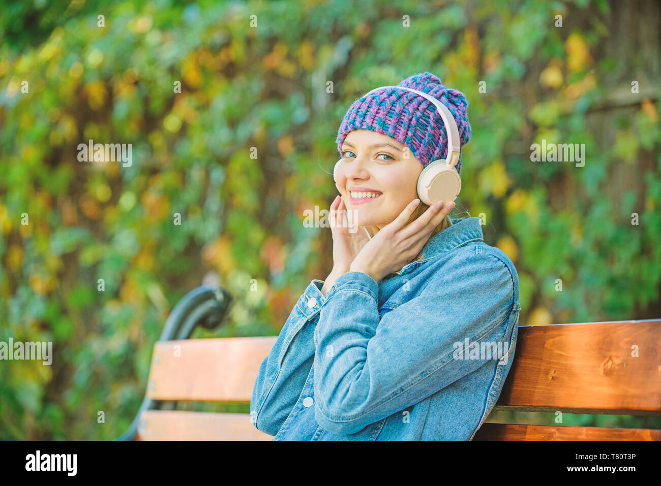 listening music in park. relax in park. hipster girl with mp3 player. modern technology instead of reading. hipster woman in headphones. audio book. style and music. Enjoying her favorite music. - Stock Image