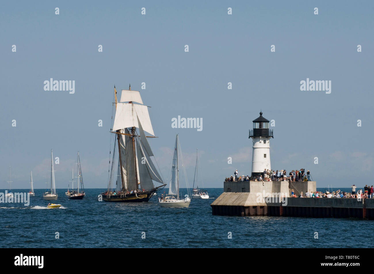 Duluth, Minnesota. Spectators watch as one of three tall ships enters the port of Duluth  to be part of the Duluth Maritime Festival. The ships are a  - Stock Image