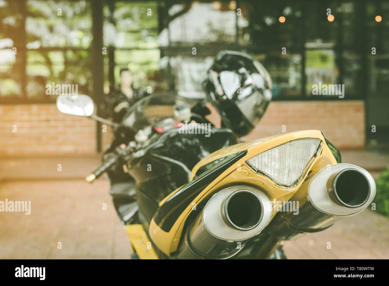 A sporty motorcycle parked in front of a coffee shop - Stock Image