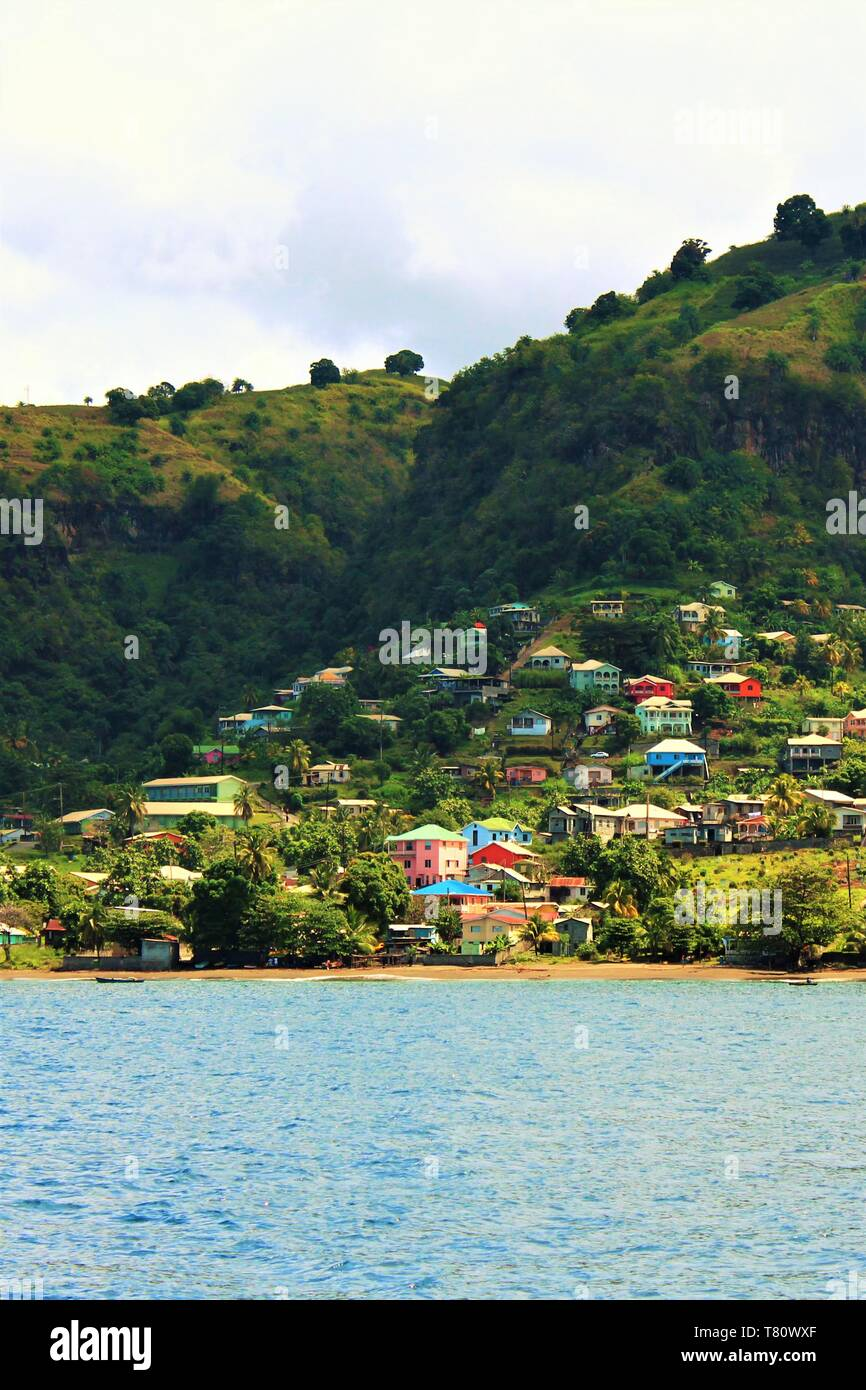 An example of the lush green hills and colorful buildings which make up the landscape of the Caribbean island of St Vincent. Stock Photo