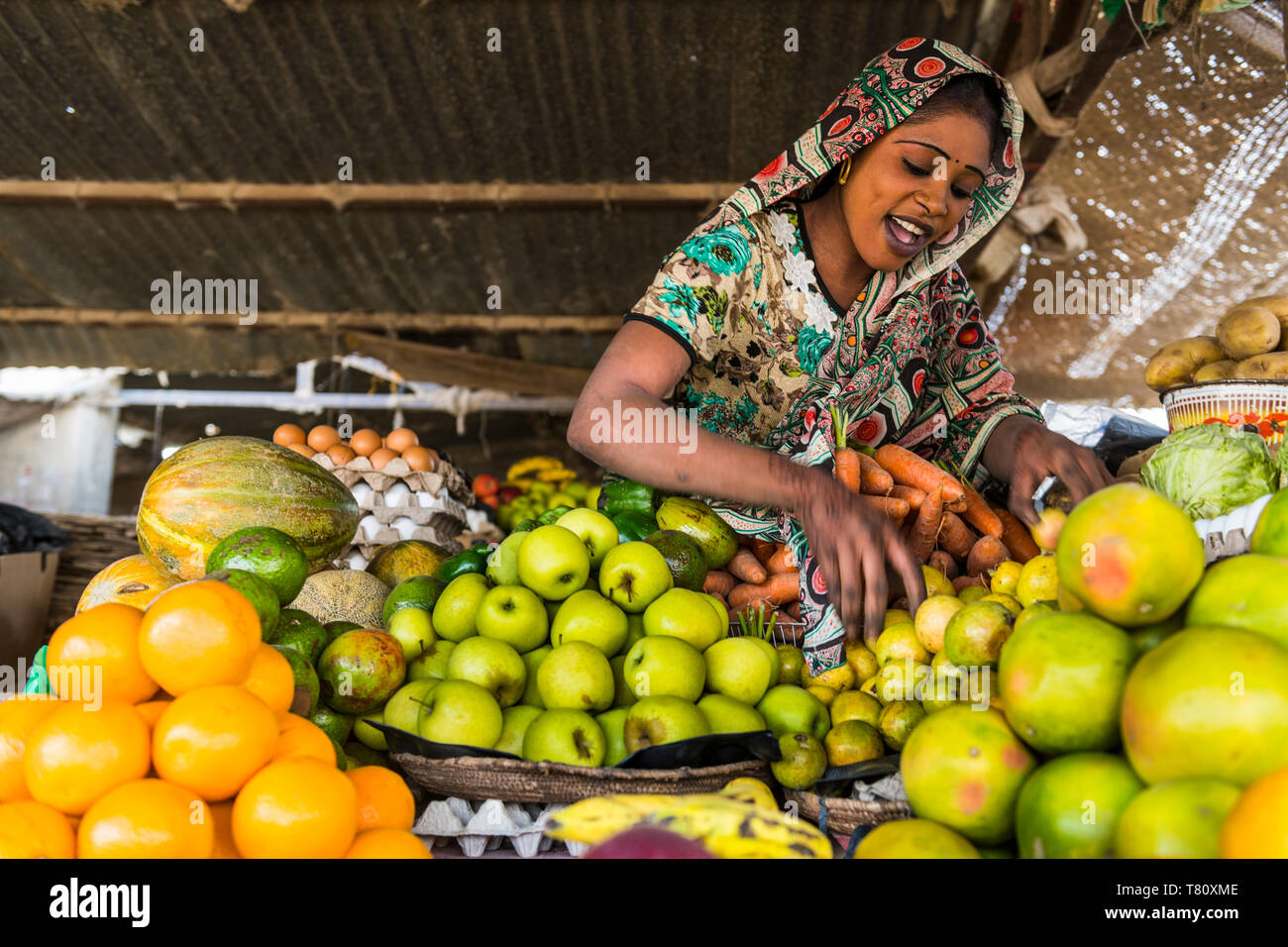 Happy sales woman on her fruit stall, Abeche, Chad, Africa - Stock Image