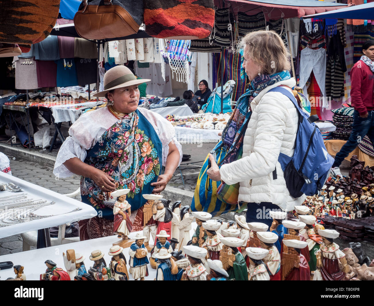 Tourist shopping at market, Plaza de los Ponchos, Otavalo, Ecuador, South America - Stock Image