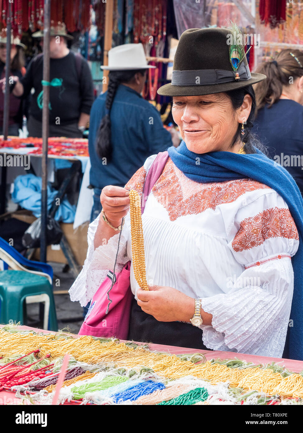 Indigenous woman buying gold necklace, market, Plaza de los Ponchos, Otavalo, Ecuador, South America - Stock Image