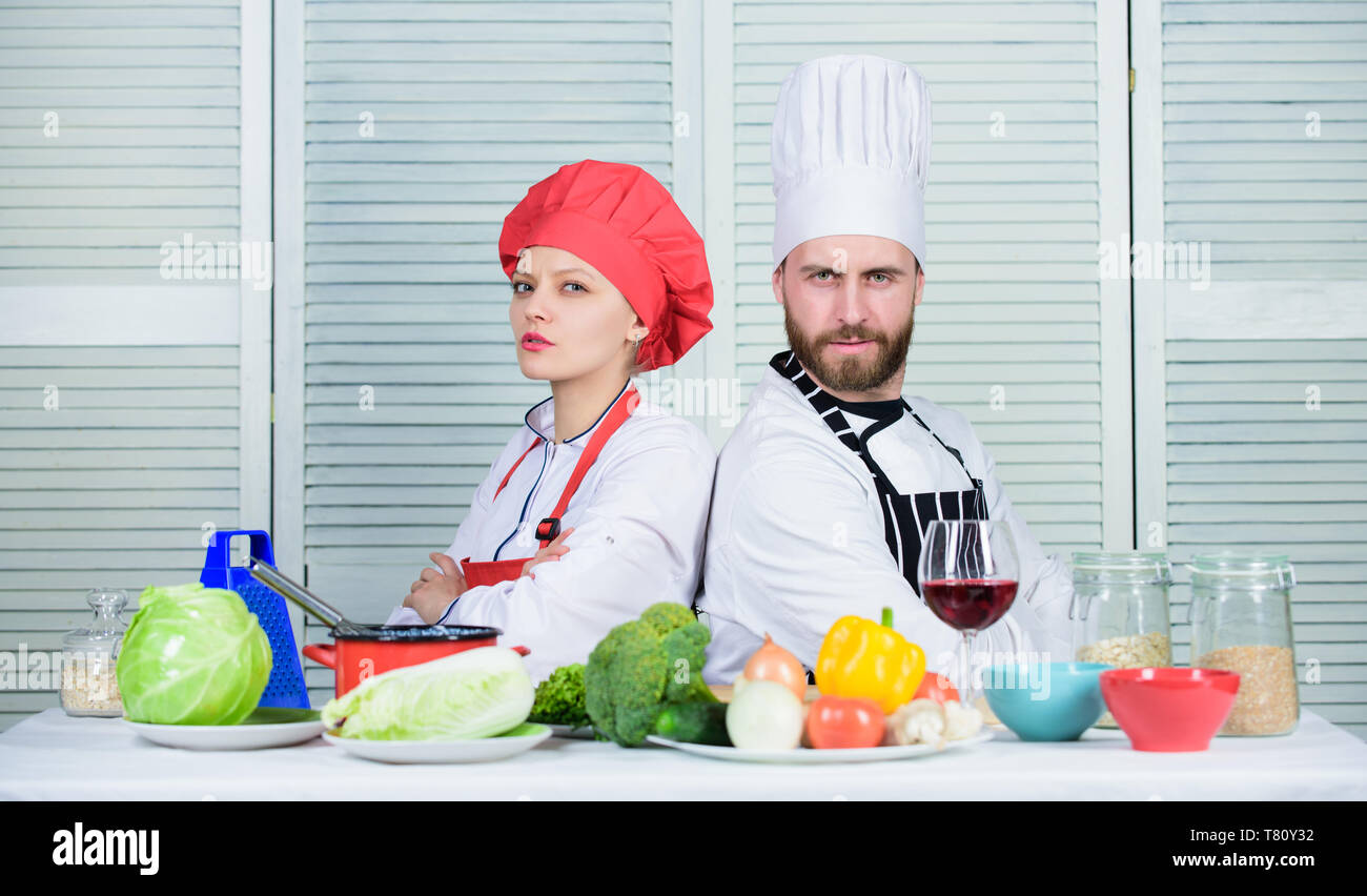 Cooking with your spouse can strengthen relationships. Woman and bearded man culinary partners. Ultimate cooking challenge. Reasons why couples cooking together. Couple compete in culinary arts. - Stock Image
