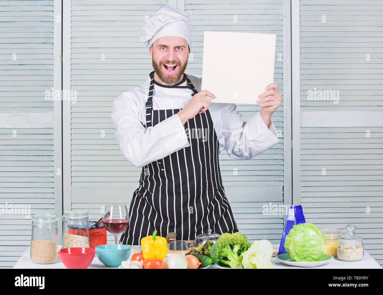 Ultimate cooking guide for beginners. Book family recipes copy space. According to recipe. Man bearded chef author of book. Chef recommend book. Culinary recipes book concept. Improve cooking skill. - Stock Image