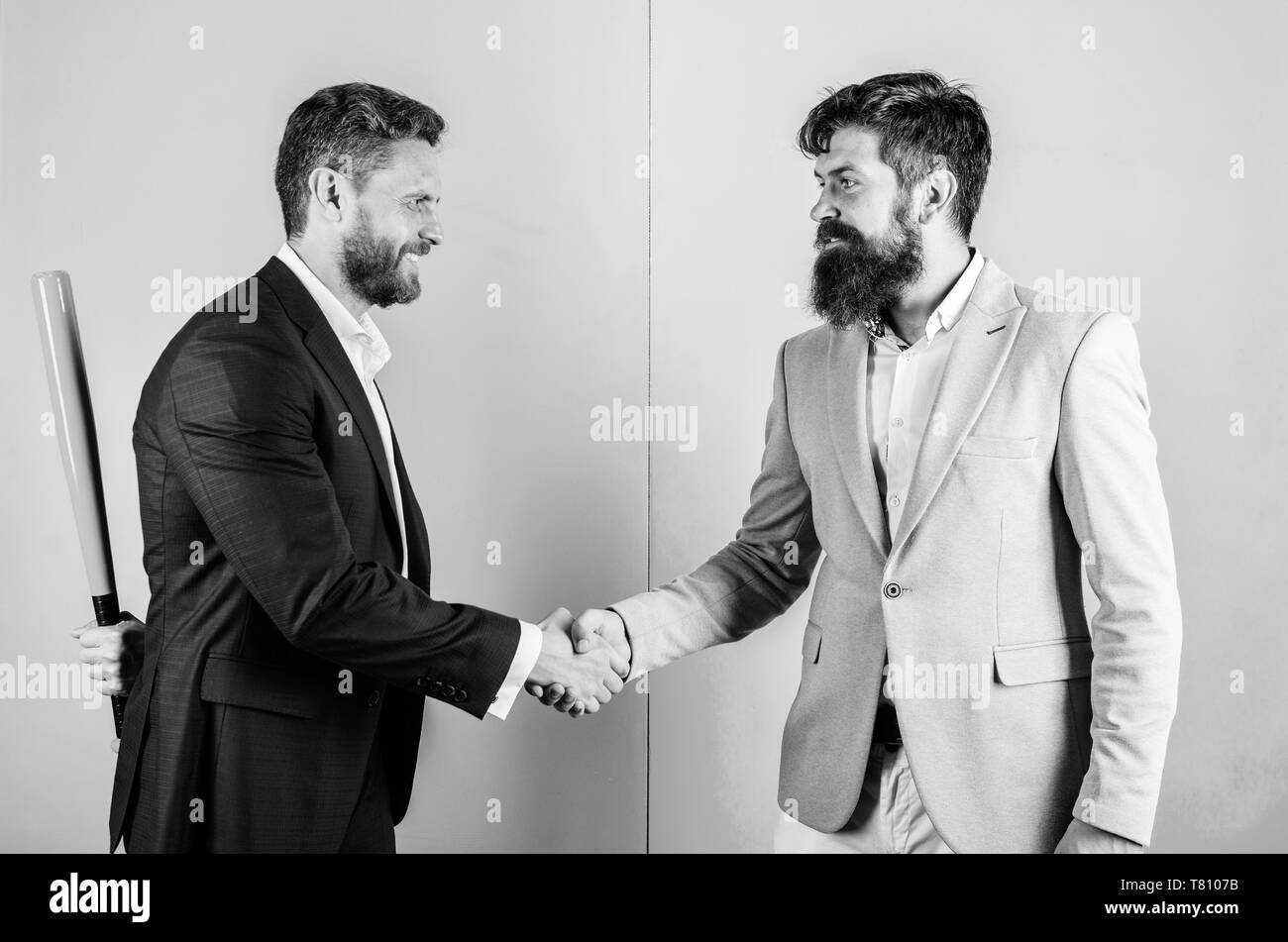 Business partners competitors office colleagues shaking hands. Tricky first impression. Do not trust him. Hidden danger. Businessman hides bat behind back while shaking hands. Hidden threat concept. - Stock Image