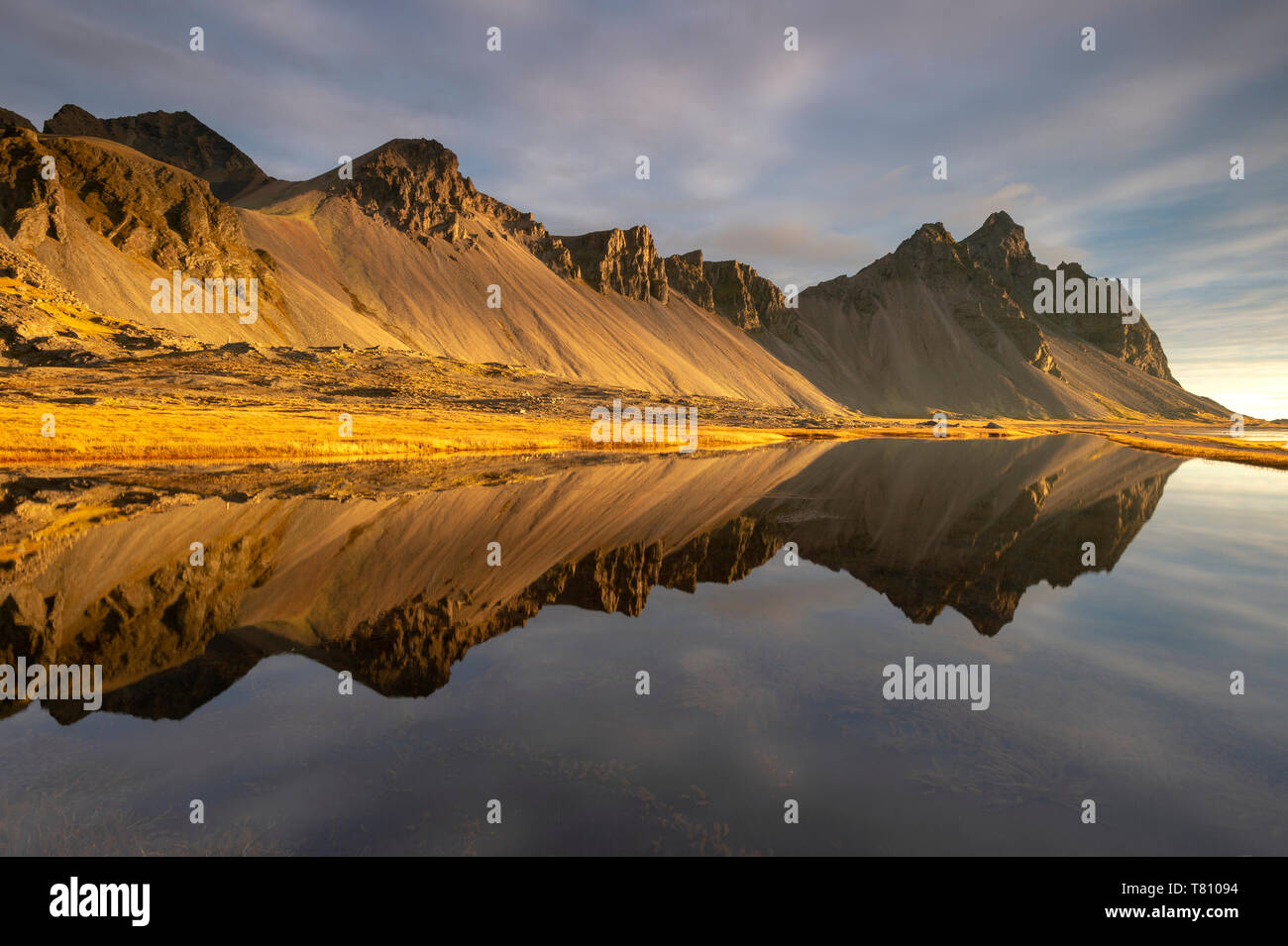View of mountains of Vestrahorn and perfect reflection in shallow water, soon after sunrise, Stokksnes, South Iceland, Iceland, Polar Regions - Stock Image