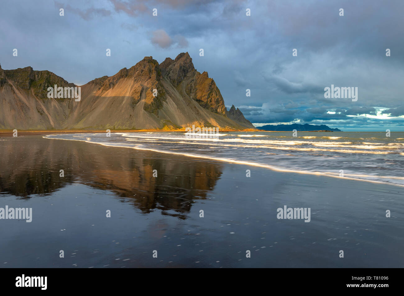 View of the mountains of Vestrahorn from black volcanic sand beach at sunset, Stokksnes, South Iceland, Iceland, Polar Regions - Stock Image