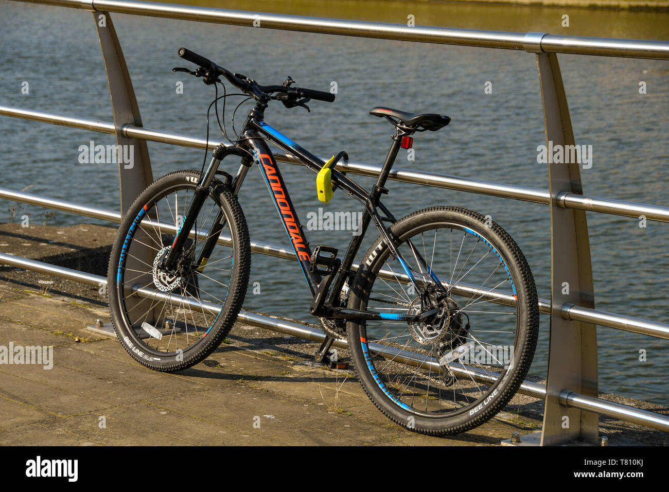 SWANSEA, WALES - JULY 2018: Bike secured to metal railings with a cycle lock to prevent theft. - Stock Image
