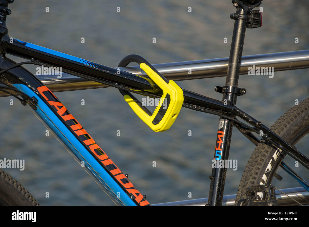SWANSEA, WALES - JULY 2018: Close up of a lock securing the frame of a bike to metal railings to prevent theft. - Stock Image