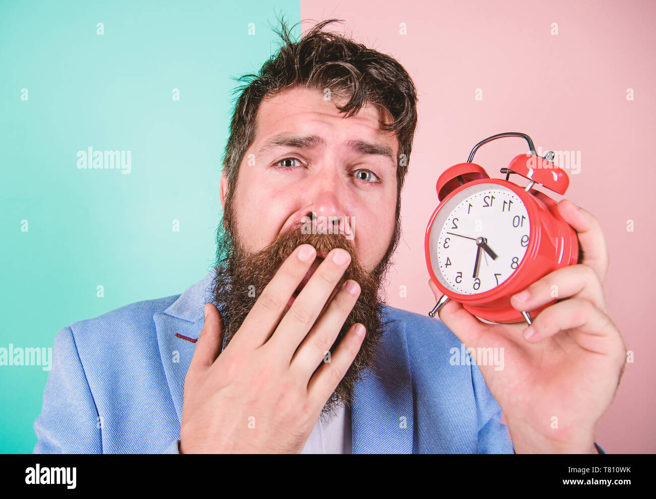 Time management skills. How much time till deadline. Time to work. Man bearded sleepy tired businessman hold clock. Stress concept. Hipster stressful working schedule. Businessman has lack of time. - Stock Image