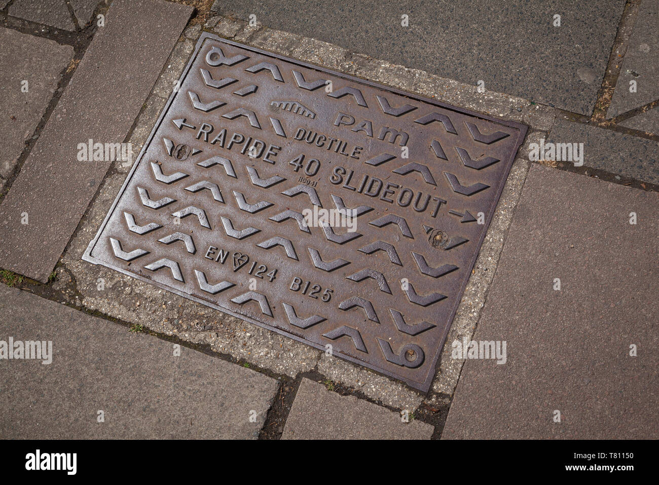 A cast-iron manhole cover marked 'Rapide 40 Slideout', 'Ductile' and 'PAM'. - Stock Image