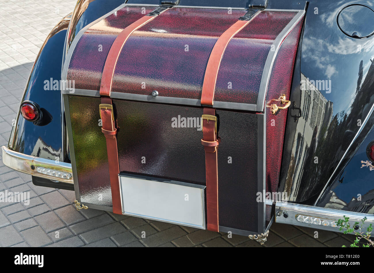 Retro old leather trunk attached to the black vintage car - Stock Image
