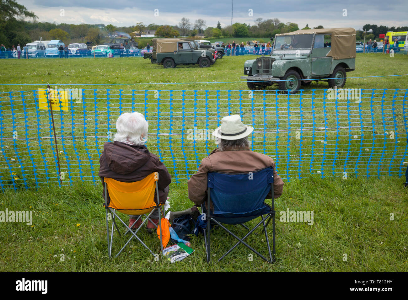 Two seated spectators watch a display of classic Land Rovers at a country show. Stock Photo