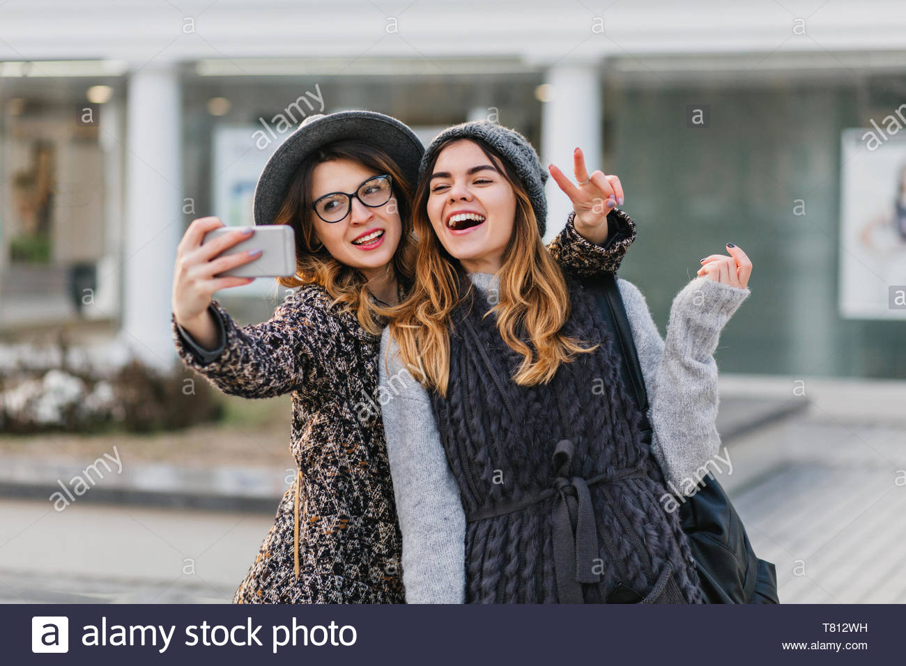 9dda980b8f05e Selfie portrait of joyful fashionable girls having fun on sunny street in  city. Stylish look