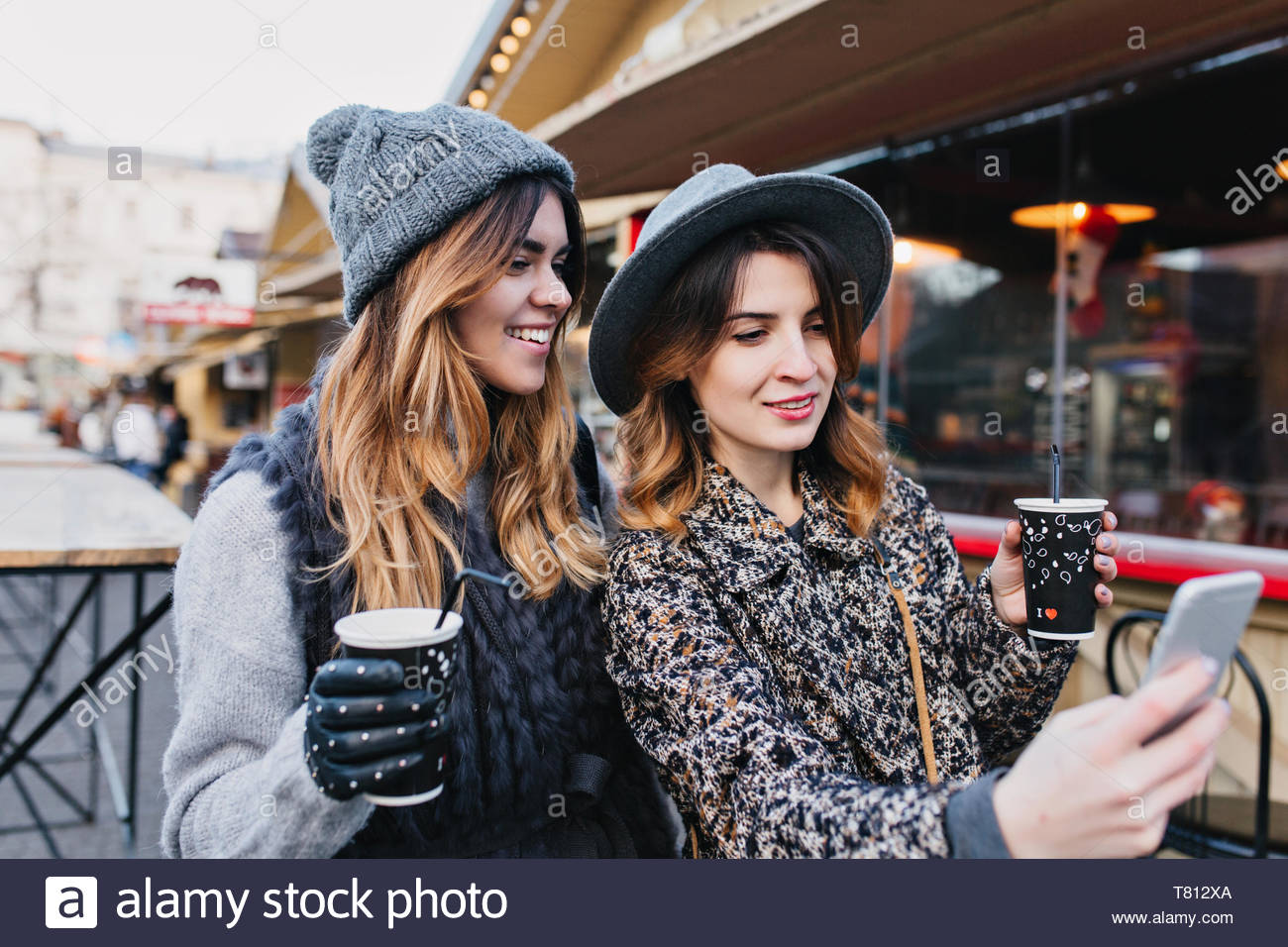Selfie portrait of joyful fashionable girls having fun on sunny street in city. Stylish look, having fun, travelling with friends, smiling, expressing true positive emotions Stock Photo