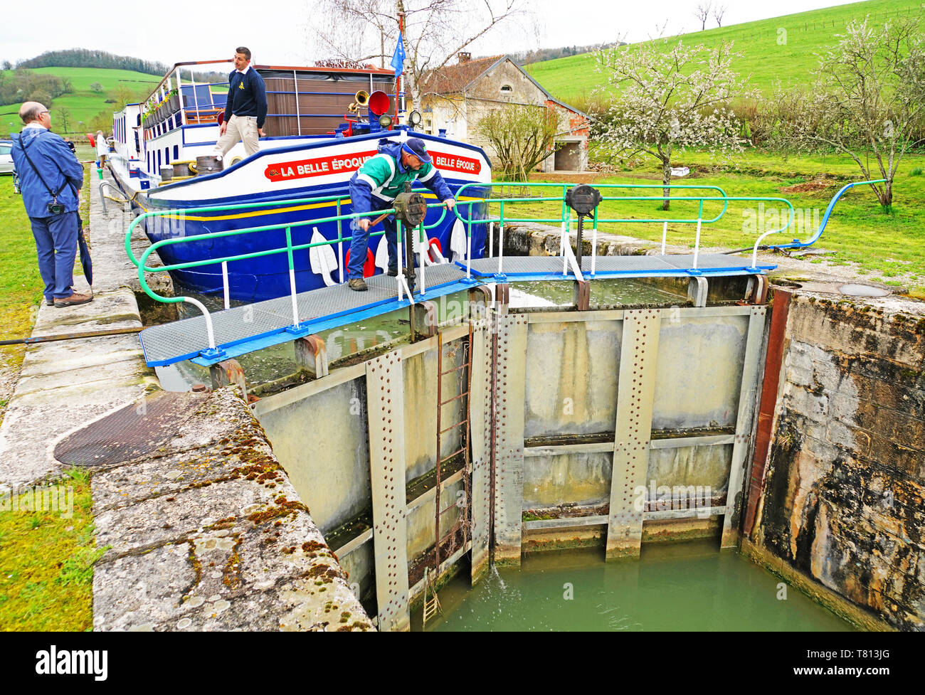 Lock keeper maually opening lock on Burgundy Canal for canal barge La Belle Epoque. - Stock Image