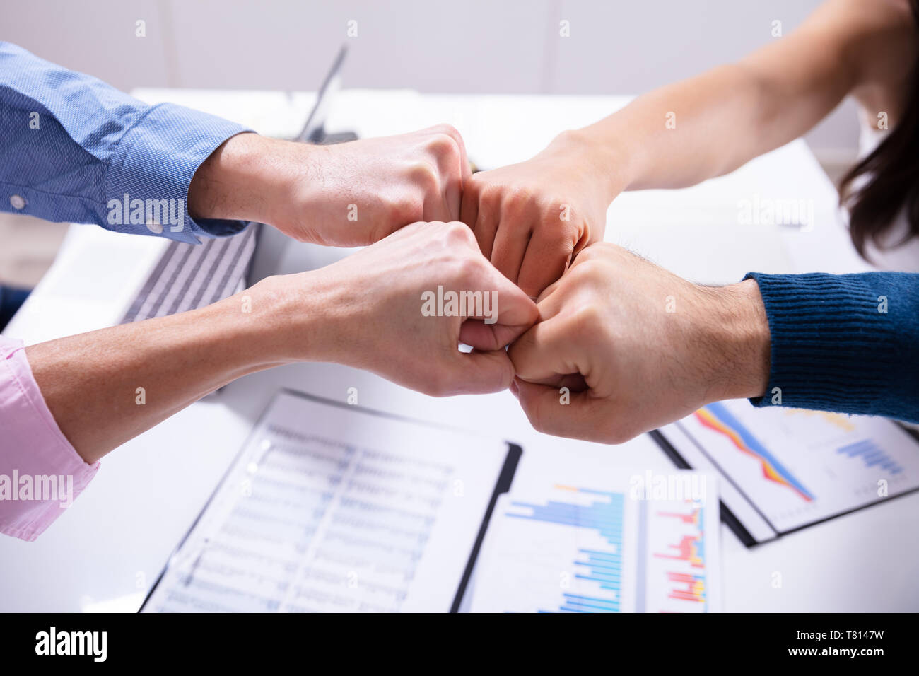 Close-up Of Businesspeople Making Fist Bump Over Desk - Stock Image