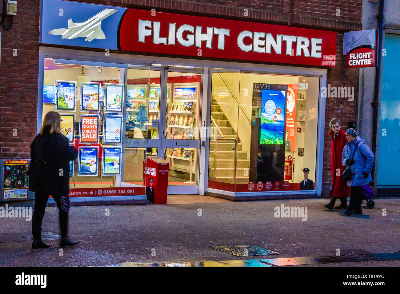 People passing the shop front exterior of a Flight Centre travel agency, Queen St, Oxford, UK. December 2018. - Stock Image