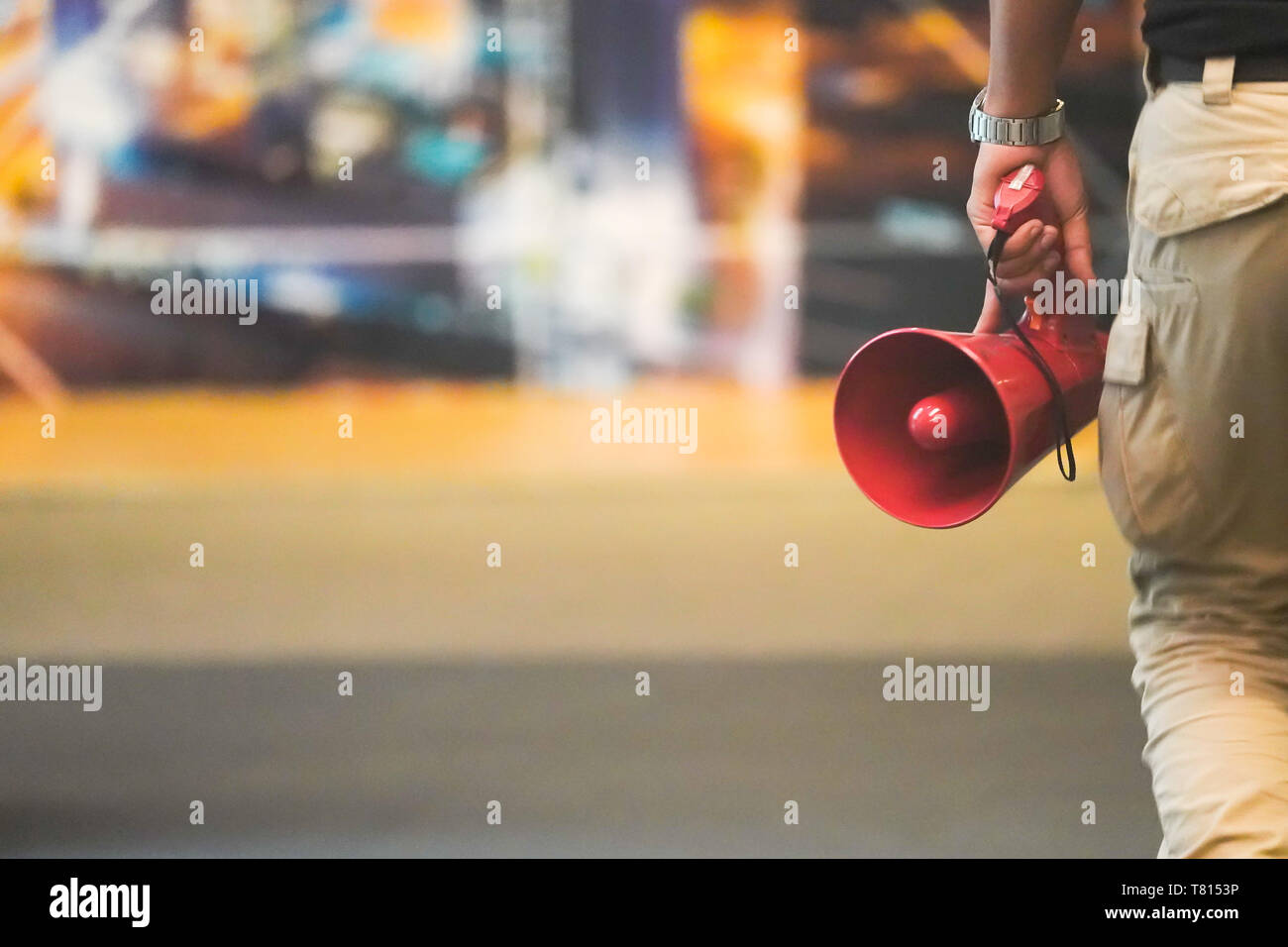 Red Megaphone in man hand with blur backround. - Stock Image