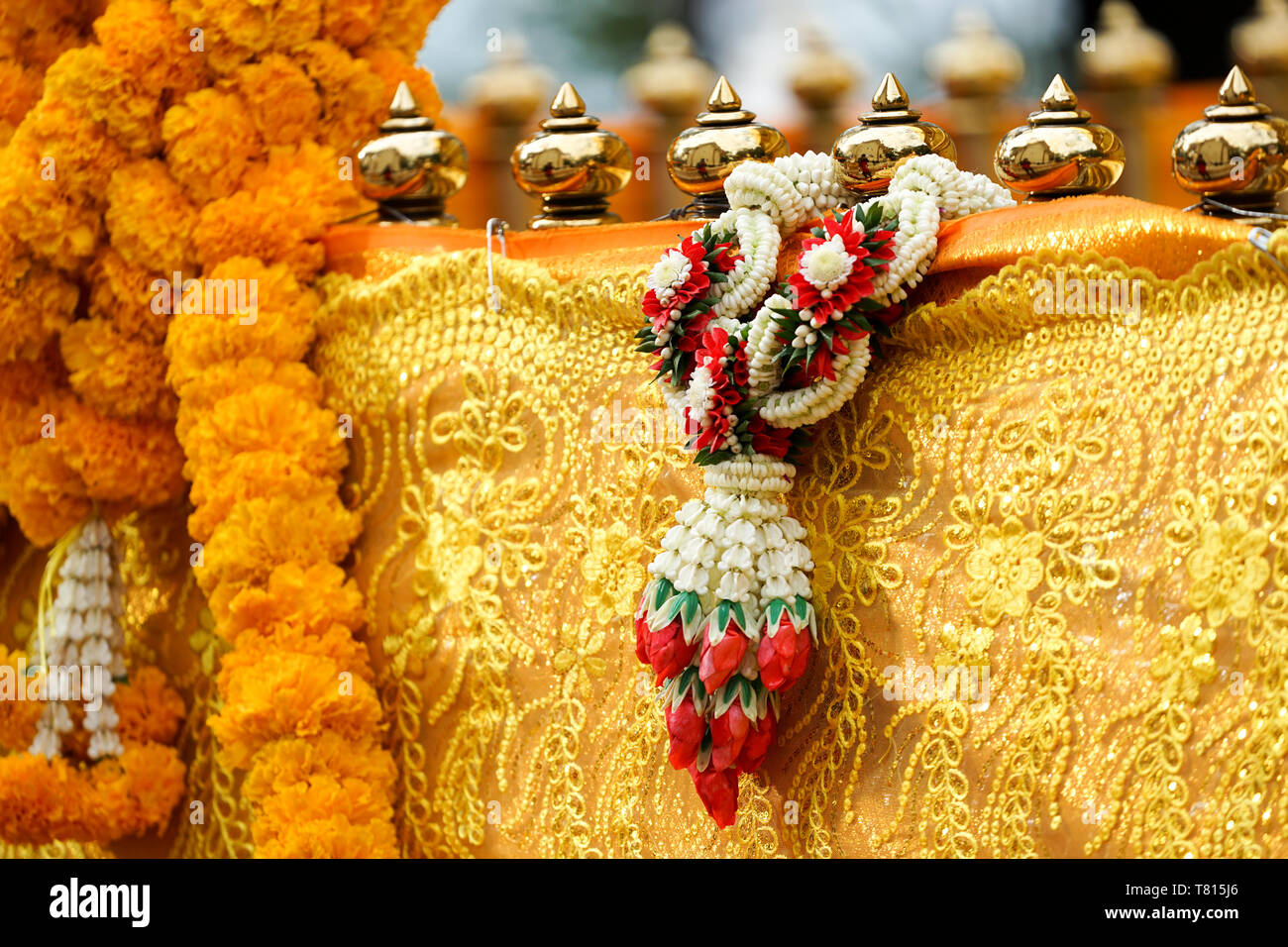 Thai luxury craft garland handmade hang on to pagoda barricade covered by yellow gold cloth. Stock Photo