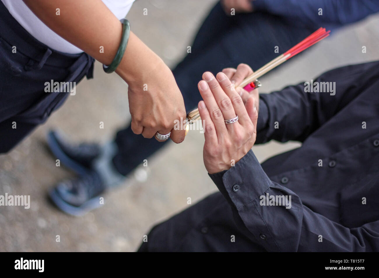 Incense in one man hand are fired by lighter on another man hand. - Stock Image