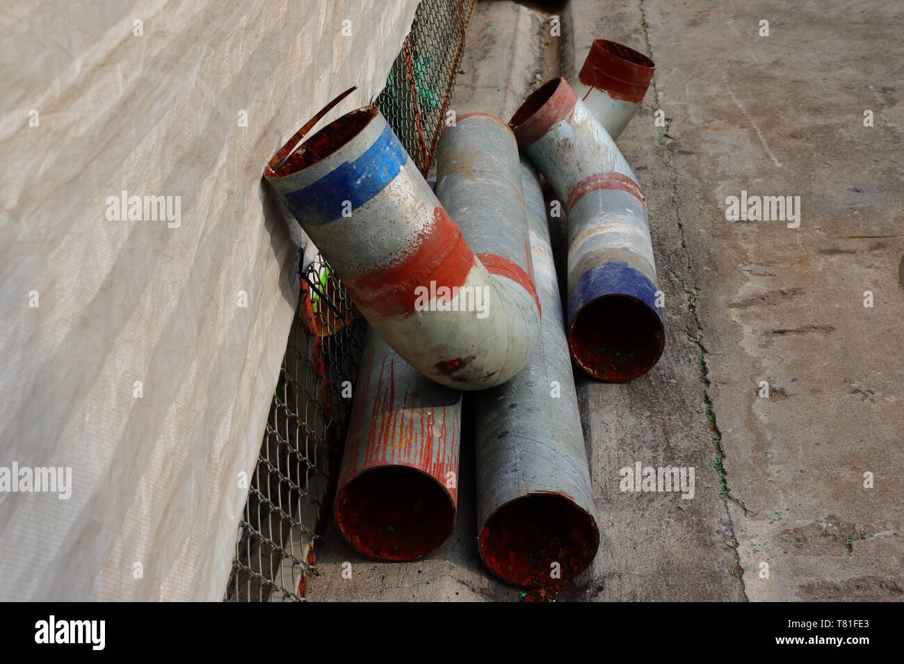 Closeup of many large metal pipes on concrete floor - Stock Image