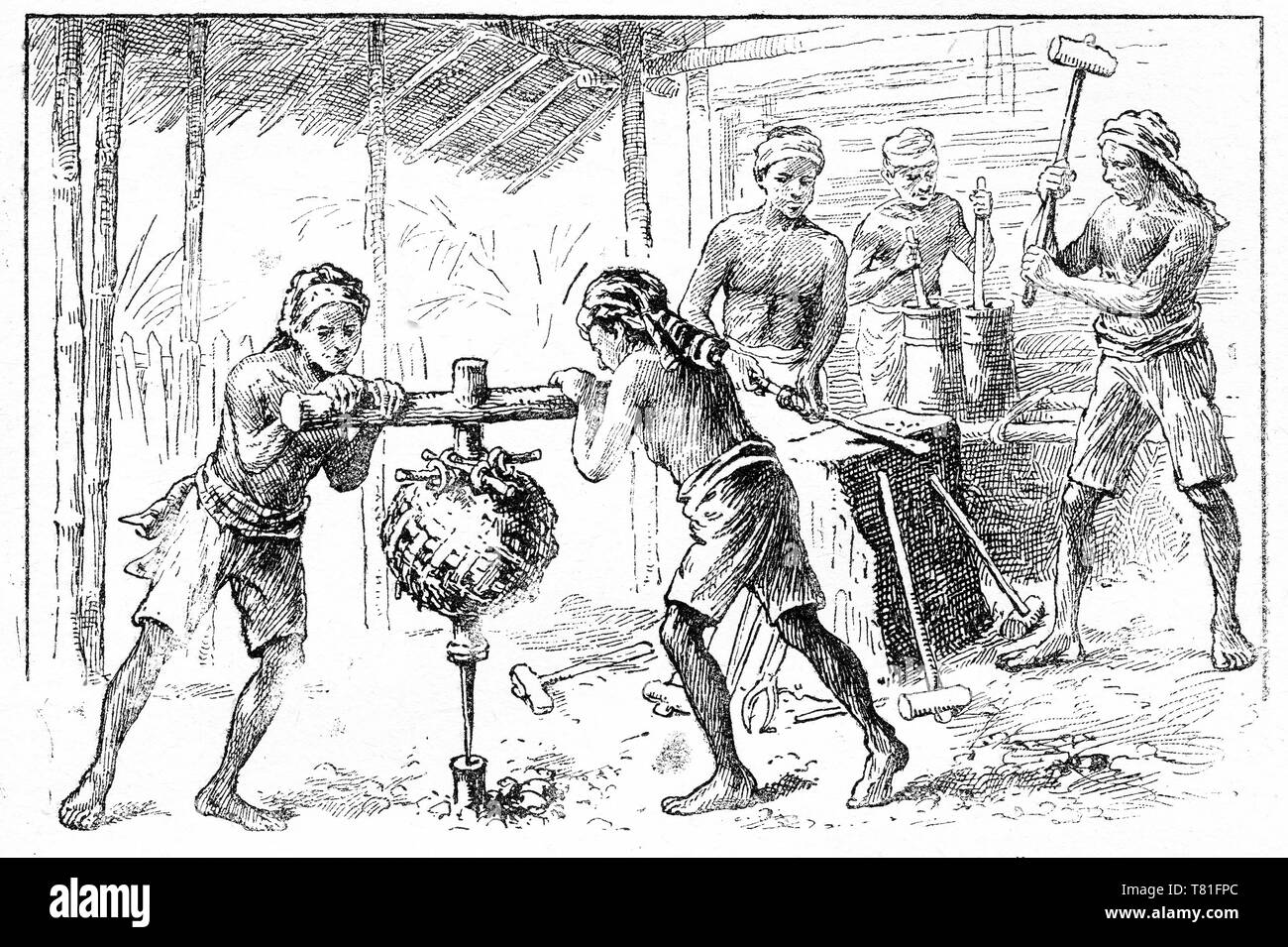 Engraving of a Asian workers in a blacksmith's shop working at an anvil. Two boys are turning a primitive weighted drill to make a hole in a piece of metal. Chatterbox magazine, 1917 - Stock Image