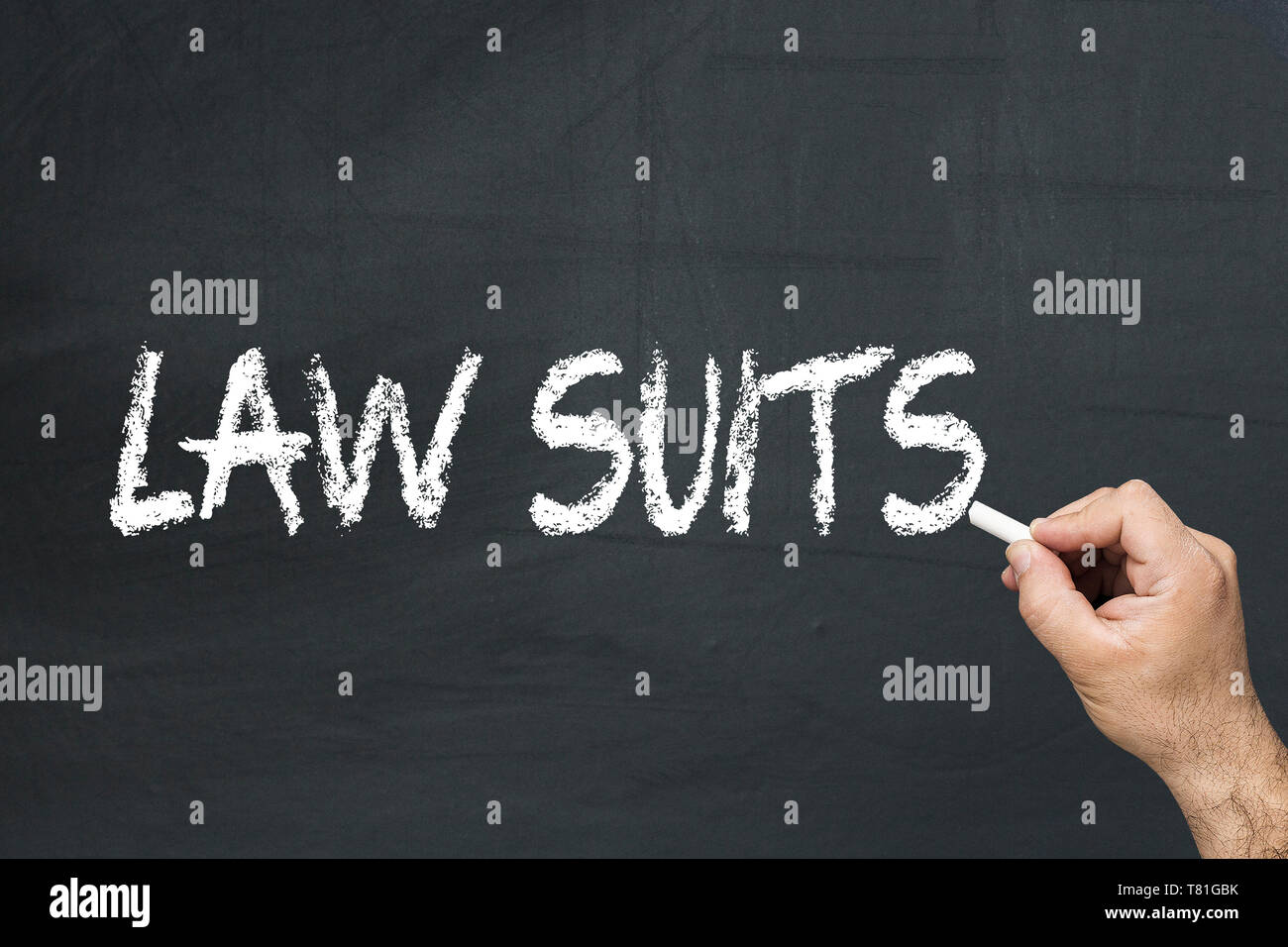 Male's hand writing text on the chalkboard: Law suits - Stock Image