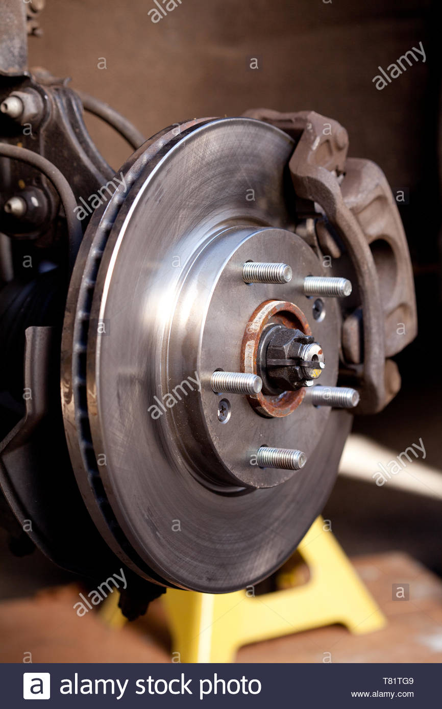Close up shot of a newly replaced brake rotor and pads for a modern car Stock Photo