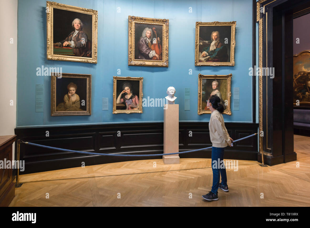 Young woman art, view of a young woman looking at 18th century portraits in the Kunsthistorisches Museum in Vienna, Austria. Stock Photo