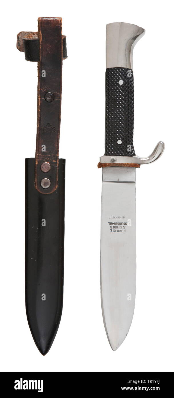 A Hitler Youth knife with motto etching and paper issue bag Maker Herbertz & Meurer, Solingen. The blade with etched motto and manufacturer's trademark. Plated hilt, black plastic grip plates with enamelled HJ-emblem. Black lacquered steel scabbard with riveted black leather hanger. Length 25 cm. Complete with factory paper issue bag (minor damage). USA-Los historic, historical, 20th century, 1930s, League of German Girls, Band of German Maidens, youth organization, youth organizations, NS, National Socialism, Nazism, Third Reich, German Reich, Germany, National Socialist, , Editorial-Use-Only Stock Photo