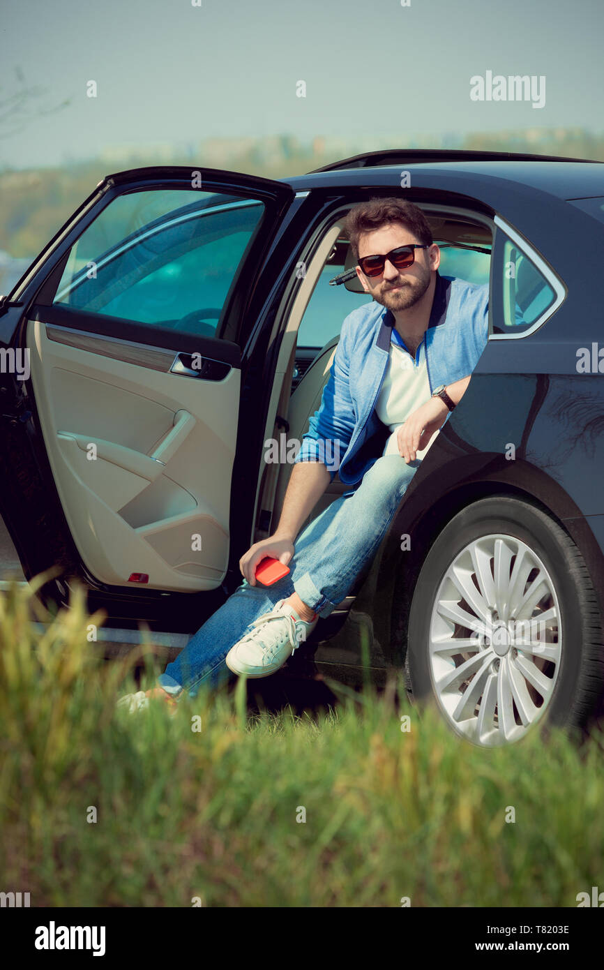Handsome smiling man in jeans, jacket and sunglasses sitting in his car with opened doors on the river's side. Preparing for weekend' trip or journey. Concept of summertime, resort, chilling. - Stock Image