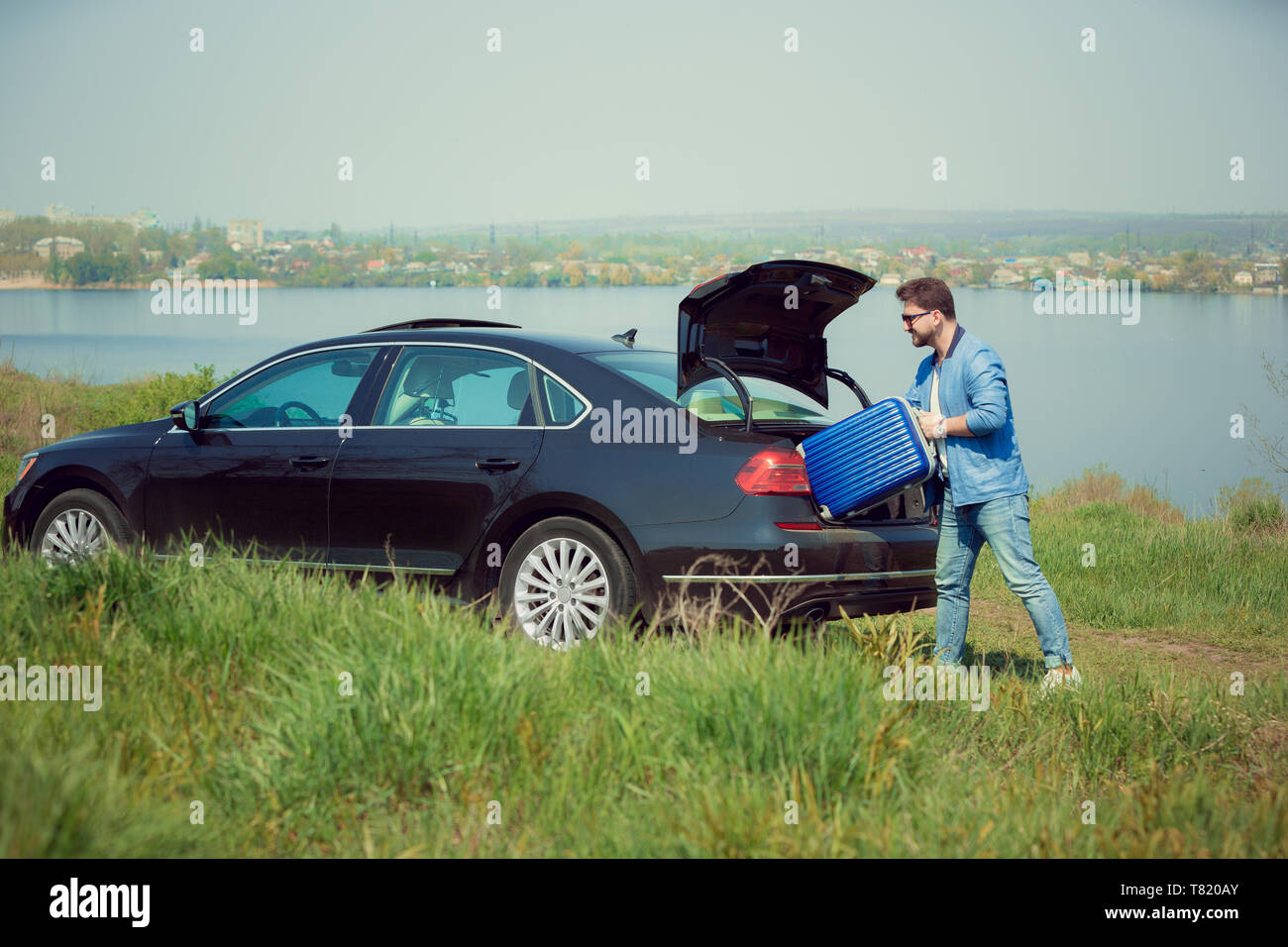 Handsome smiling man in jeans, jacket and sunglasses going to vacations, loading his suitcase in car trunk on the river's side. Preparing for weekend' trip. Concept of summertime, resort, chilling. - Stock Image