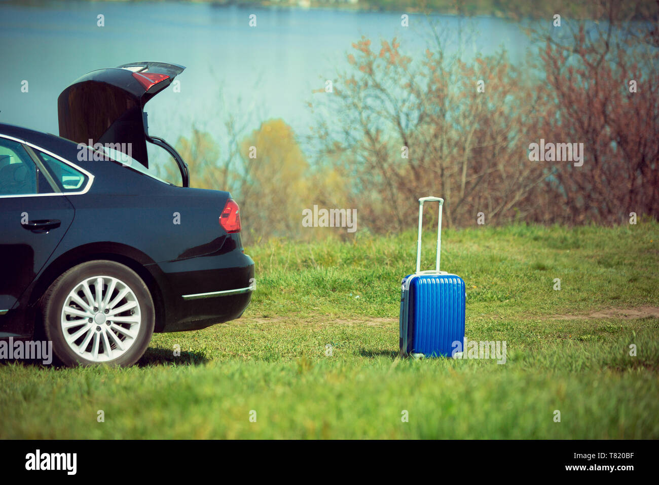 View of modern black car and blue suitcase on the river's side in sunny day. Preparing for weekend' trip or journey. Concept of summertime, resort, chilling. - Stock Image