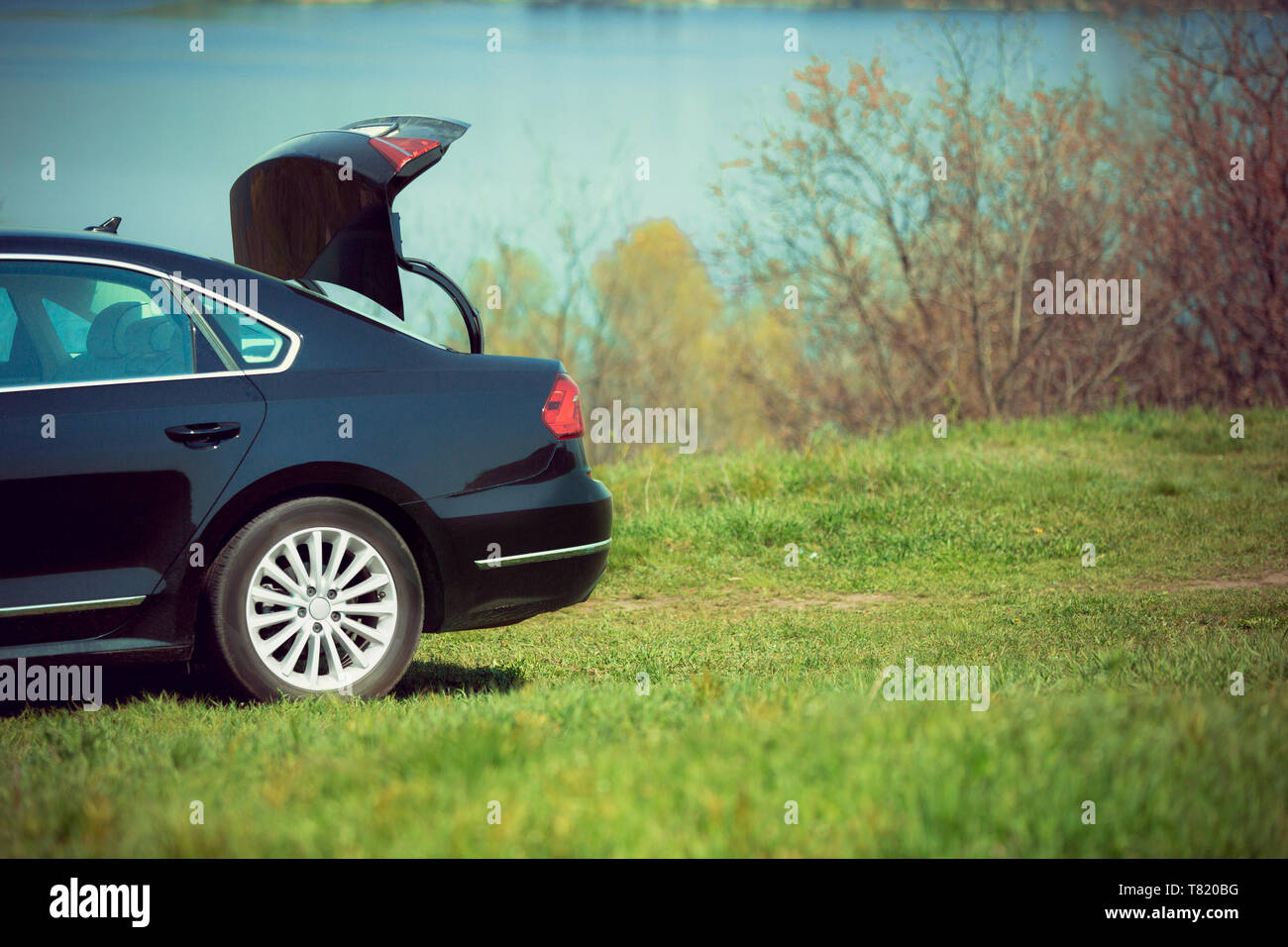 View of modern black car on the river's side in sunny day. Preparing for weekend' trip or journey. Concept of summertime, resort, chilling. - Stock Image