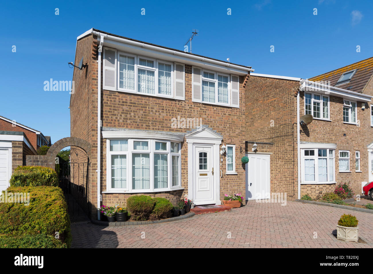 Small modern brick detached house with garage separating it from a neighbouring house in West Sussex, England, UK. - Stock Image