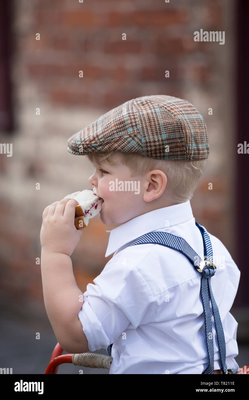Close up of cute little boy in 1940's costume wearing flat cap & braces eating big jam sandwich, Black Country Museum, 1940 wartime event, summer '18. - Stock Image