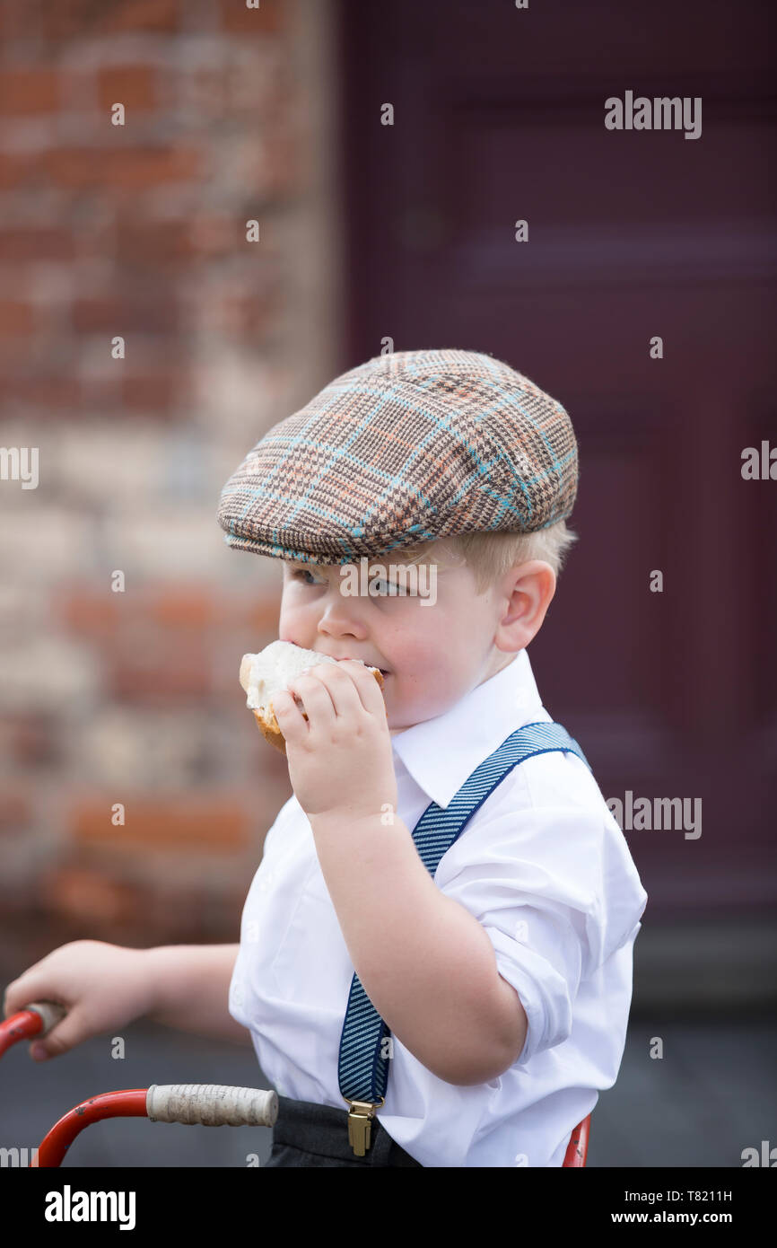 Close up of cute little boy in 1940's costume wearing flat cap & braces isolated outdoors, eating big jam sandwich, Black Country Museum, WWII event. - Stock Image