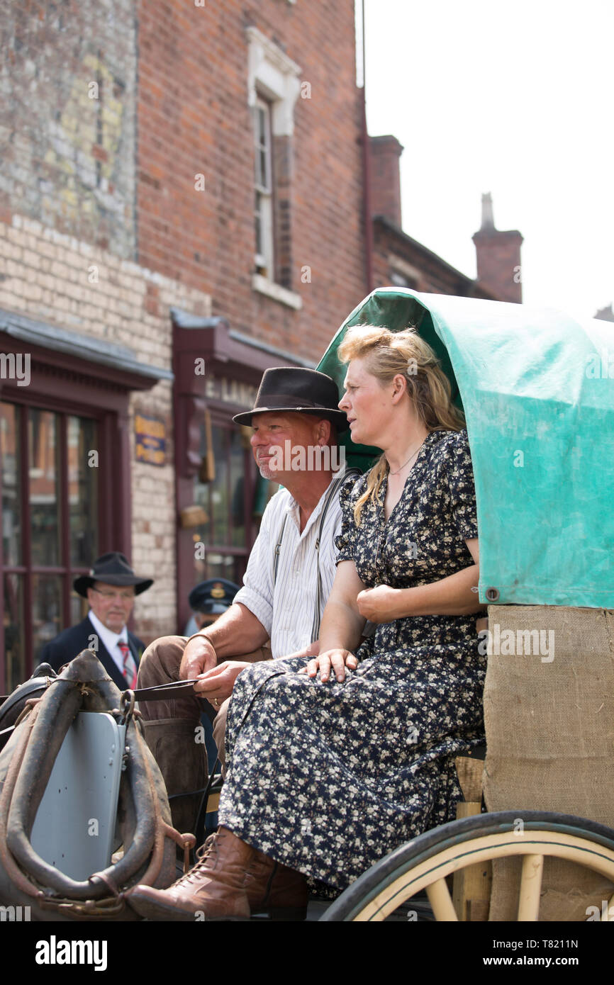 Close up of married couple seated in wagon pulled by horse outdoors in vintage street at Black Country Museum, Dudley, UK, 1940's weekend, summer 2018. - Stock Image