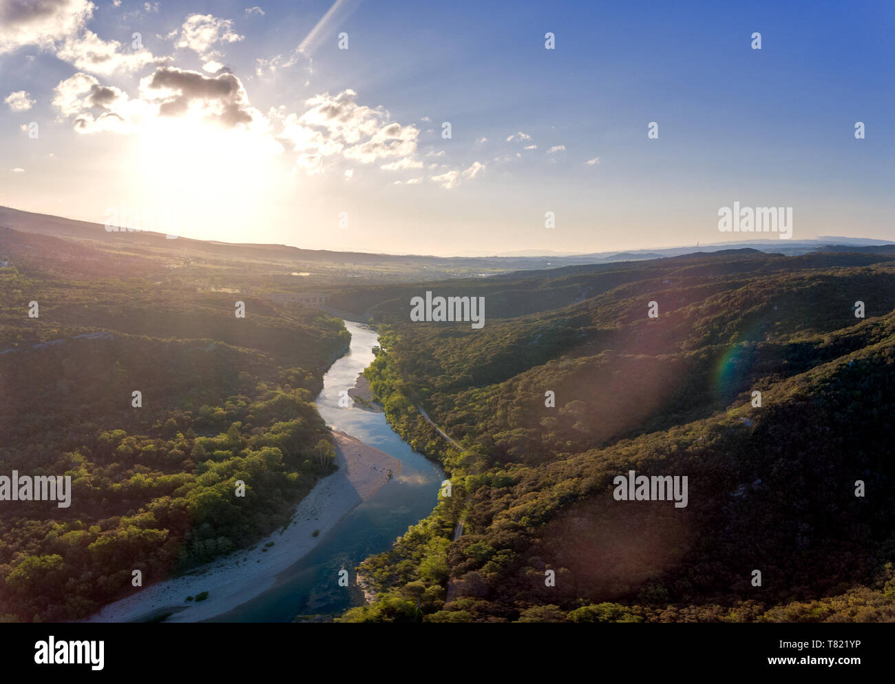 Stunning aerial drone shot of the Rhone river at sunrise. The river reflects the early morning sun and the river gorge is forested and green. An old r Stock Photo