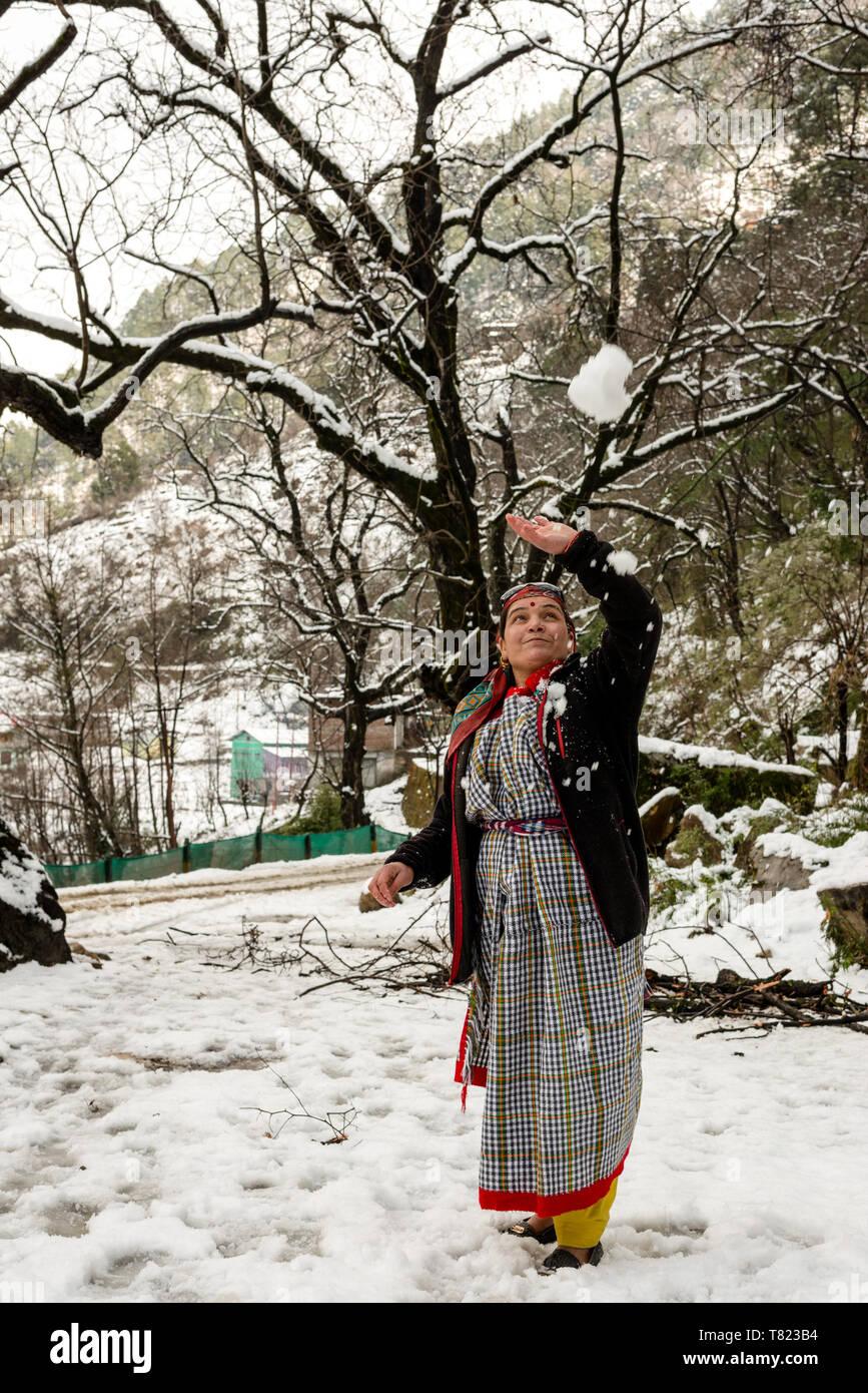 Kullu, Himachal Pradesh, India - Feburuary 08, 2019 : Woman playing with snow in mountains - Woman in Traditional Himachali Dress - India - Stock Image