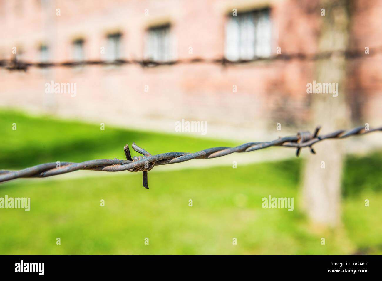 AUSCHWITZ (OSWIECIM), POLAND - APRIL 18, 2019: Electric fence and barracks Auschwitz I (main camp) in Oswiecim, Poland - Stock Image