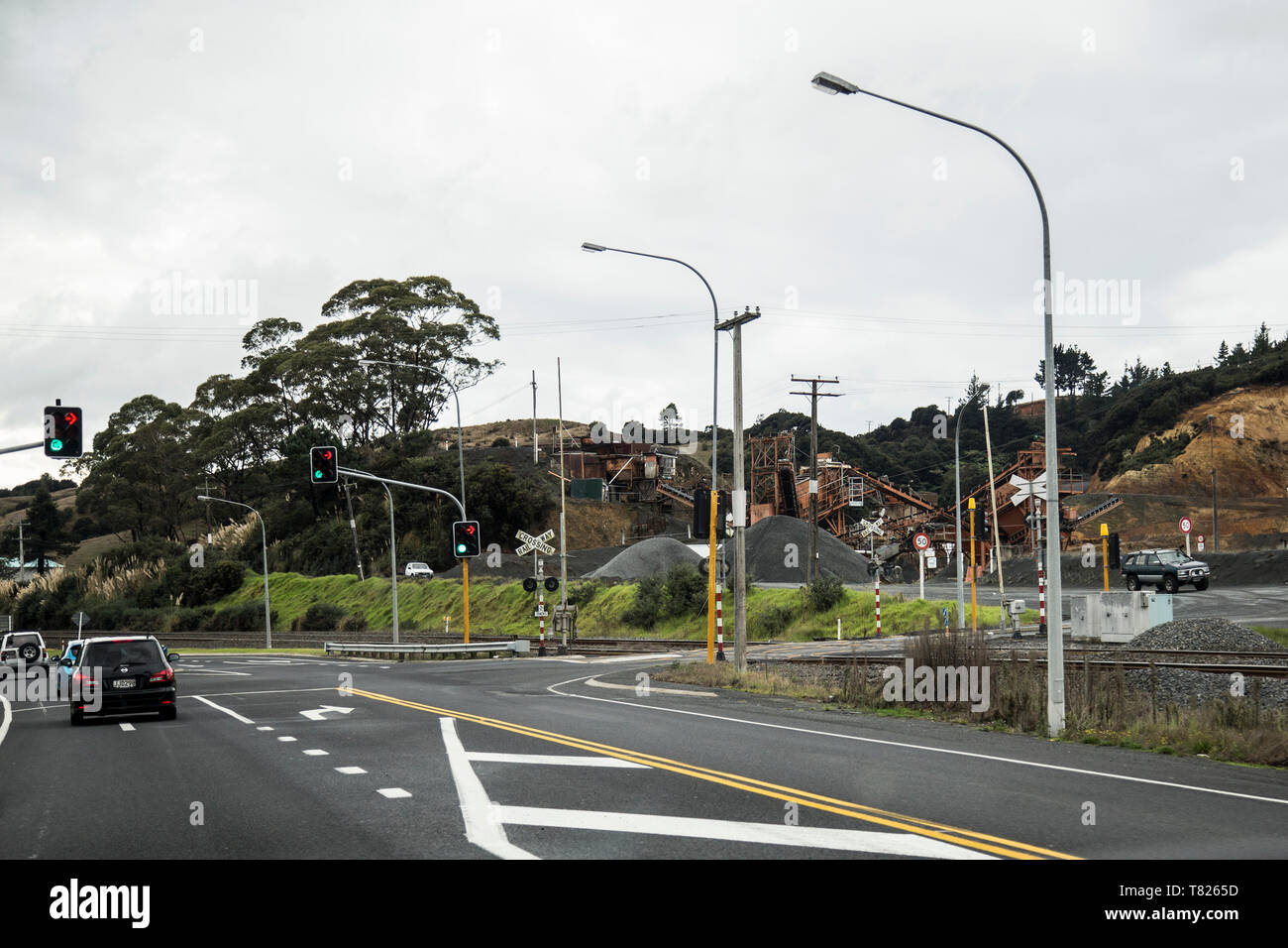 Huntly Quarry on State Highway 1 heading north on Easter weekend. Traffic lights and intersection with railroad crossing on the right. Overcast. - Stock Image
