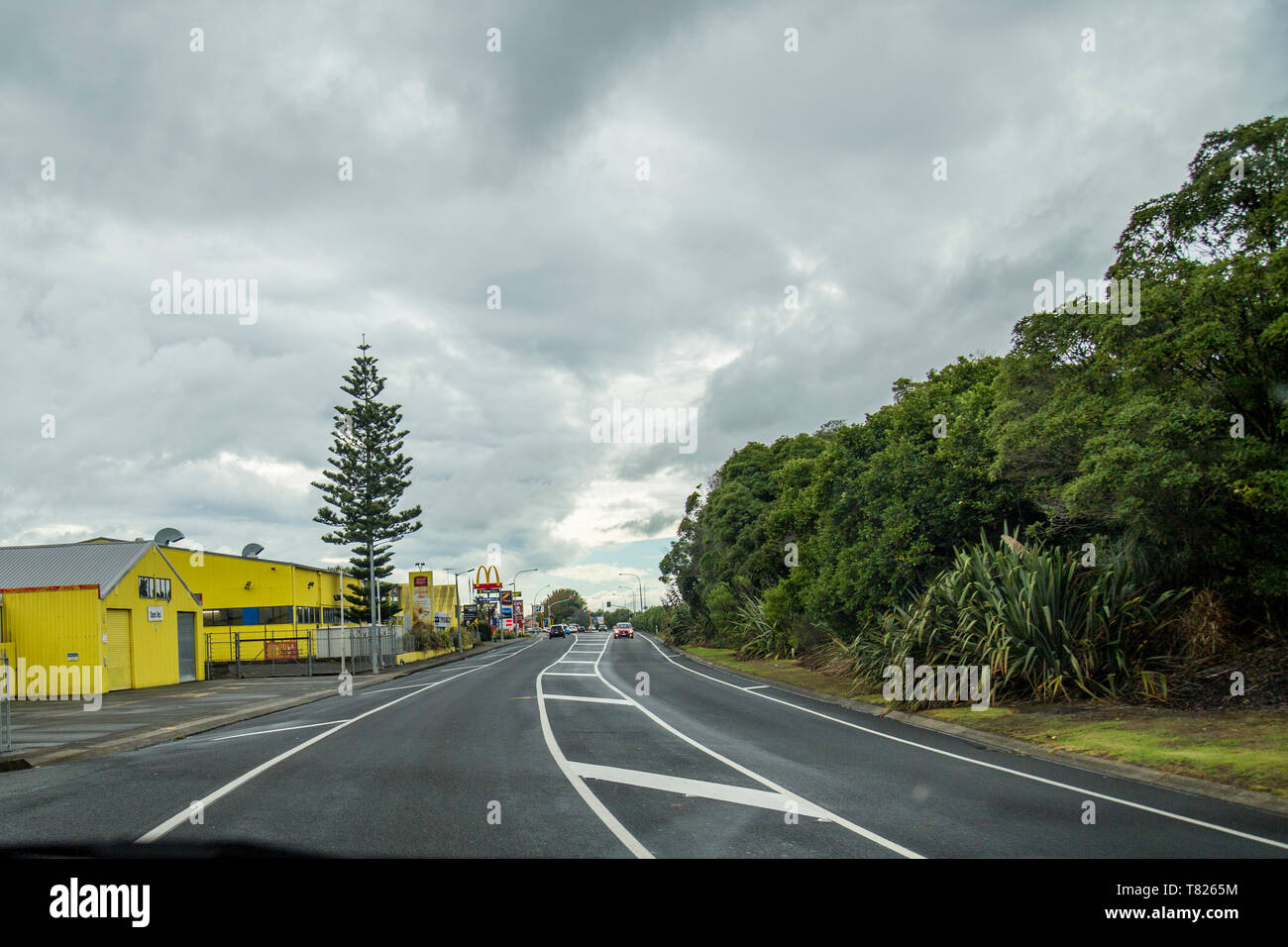 Huntly, Waikato SH1. Driving past large yellow industrial building, Ernest Adams Gluten Free bakery facility, also makes Vogels and Quality Bakers - Stock Image