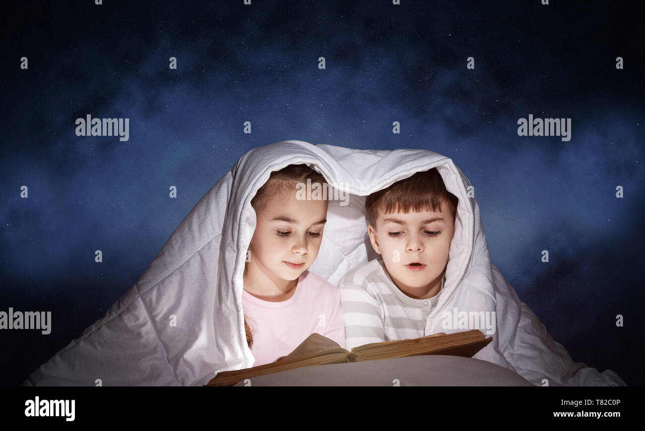 Engrossed little girl and boy reading book - Stock Image