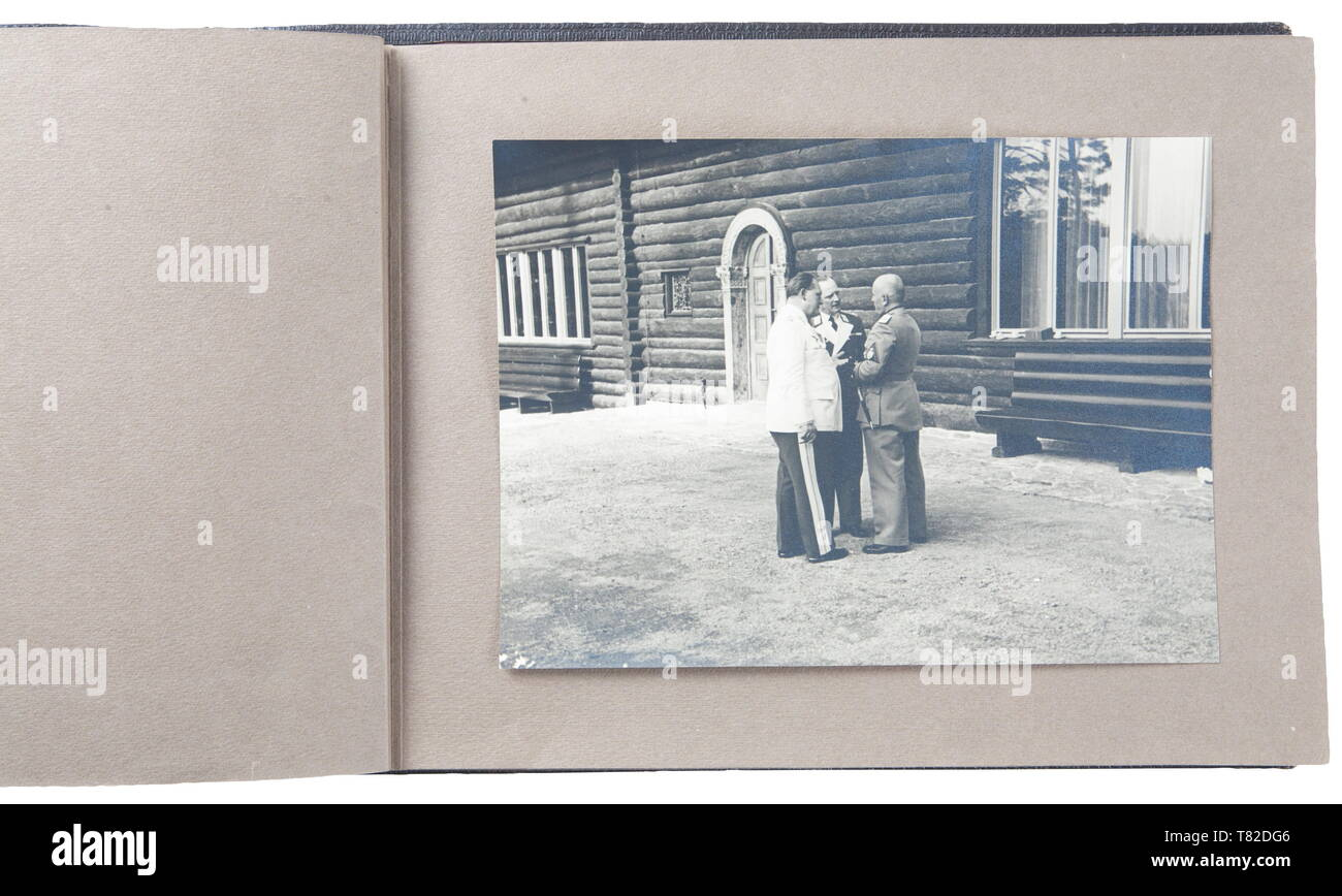 """Hermann Göring - A photo album of Mussolini's official visit to Carinhall Large format photo album (34 x 24 cm) with brown leather cover with gold-embossed """"MUSSOLINI BEI GOERING IN KARINHALL"""", """"28 SEPTEMBER 1937"""" and """"BILDBERICHT VON CARLO CARLETTI"""". Album consists of eighteen 17 x 23 cm black and white photos. Photos are of a casual/informal style and feature Hermann Göring, Emma Göring, Mussolini, Count Ciano, Achille Starace, Luftwaffe Generals Milch, Stumpf, and Bodenschatz, Paul Schmidt, SS General Dietrich, and more. From the possession of a US officer of the 101st A, Editorial-Use-Only Stock Photo"""