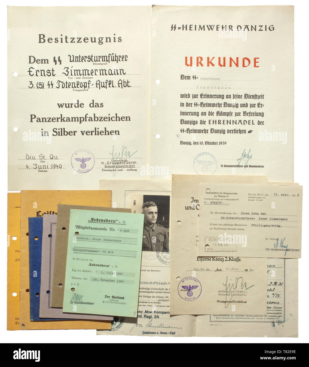 """The estate of Untersturmführer Ernst Zimmermann - Heimwehr Danzig Bicolour rendered document for the (tr) """"Honour Pin"""" of SS-Heimwehr Danzig. Document number """"1415"""" with original signature of the commander, Hans F. Goetze, issued on 10 October 1939. Also the award document for the Iron Cross 2nd Class while with """"3./(s) SS-Totenkopf-Aufkl.-Abtlg."""" with original signature of Gruppenführer and Generalleutnant of the Waffen-SS Theodor Eicke, issued on 22 June 1940 while with SS-Division """"Totenkopf"""". Included is a decorative award document for the Panzer Assault Badge in Silver, Editorial-Use-Only Stock Photo"""