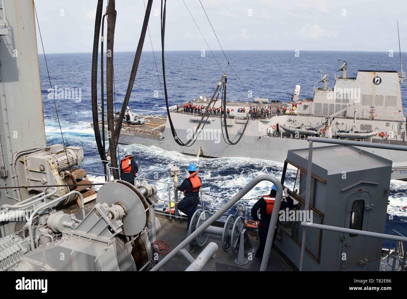 190508-N-WF604-204 SOUTH CHINA SEA (May 8, 2019) -- Civilian mariners onboard the Lewis and Clark-class dry cargo and ammunition ship USNS Richard E. Byrd (T-AKE 4) observe fuel transfer during a replenishment-at-sea with guided missile destroyer USS William P. Lawrence (DDG 110) on May 8. Military Sealift Command fleet replenishment dry cargo and ammunition ships provide support to customers via underway and vertical replenishments. (Photo by David Wyscaver) - Stock Image