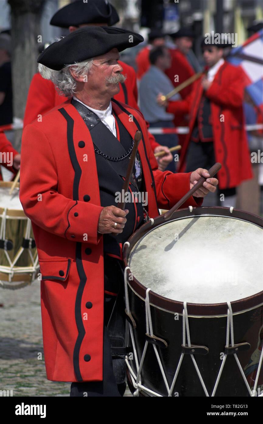 A man in a historical costume playing on a large snare drum. Ein Mann in einem historischen Kostüm, der auf einer großen Snaredrum spielt. Werblista - Stock Image